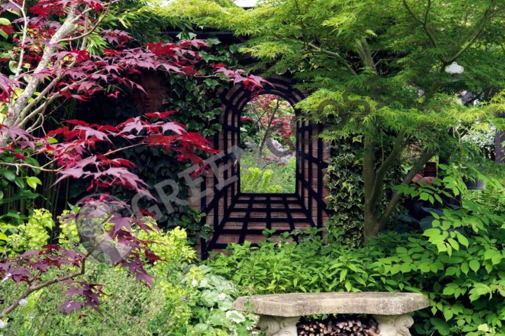 Между ветками небольших деревьев на стене висит зеркало в раме, зрительно расширяющее перспективу. Зеркало отражает интерьер сада, отчего он кажется просторным.